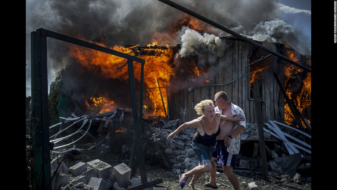People escape from a fire at a house that was destroyed by an air attack in the Ukrainian village of Luhanskaya. Melnikov's photos show how civilians have been affected by the conflict between Ukraine and pro-Russian rebels.