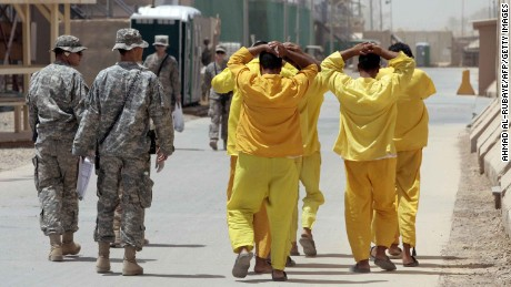 Iraqi prisoners are escorted by US soldiers within US-run detention centre, Camp Cropper, on the outskirts of Baghdad on June 23, 2009.