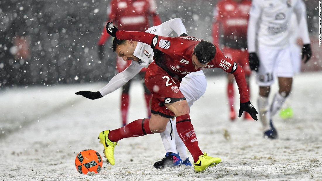 Caen midfielder Steed Malbranque, in white, competes for the ball with Dijon's Romain Amalfitano during a French league match in Dijon on Saturday, February 11.