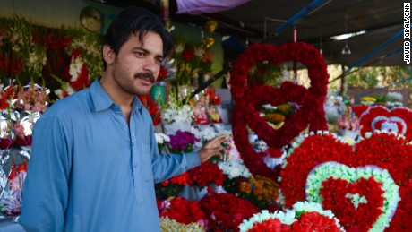 Sultan Zaib in front of his garlands of roses.