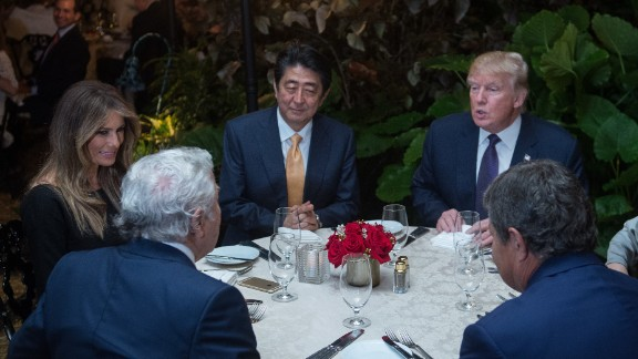 US President Donald Trump (facing right), Japanese Prime Minister Shinzo Abe (facing center), US First Lady Melania Trump (L), and Robert Kraft (2nd-L), owner of the New England Patriots, sit down for dinner sat Trump