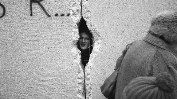 A young man peers into East Berlin though a hole in the Berlin Wall at the effective end of the city's partition, 31st December 1989. (Photo by Steve Eason/Hulton Archive/Getty Images)