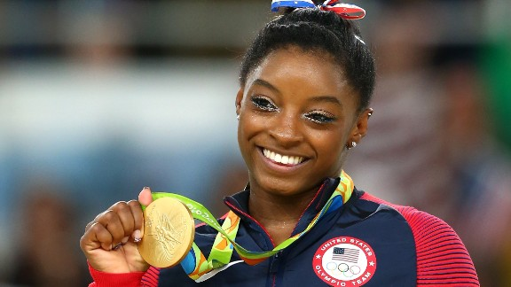 RIO DE JANEIRO, BRAZIL - AUGUST 16:  Gold medalist Simone Biles of the United States celebrates on the podium at the medal ceremony for the Women's Floor on Day 11 of the Rio 2016 Olympic Games at the Rio Olympic Arena on August 16, 2016 in Rio de Janeiro, Brazil.  (Photo by Alex Livesey/Getty Images)
