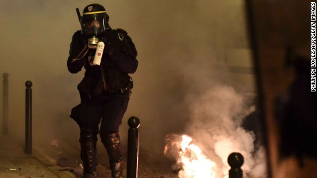 A riot policeman holds a tear gas canister at the Paris protest.