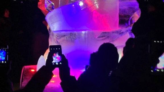 People use smartphones on on February 16, to take photos of an ice sculpture in Pyongyang.