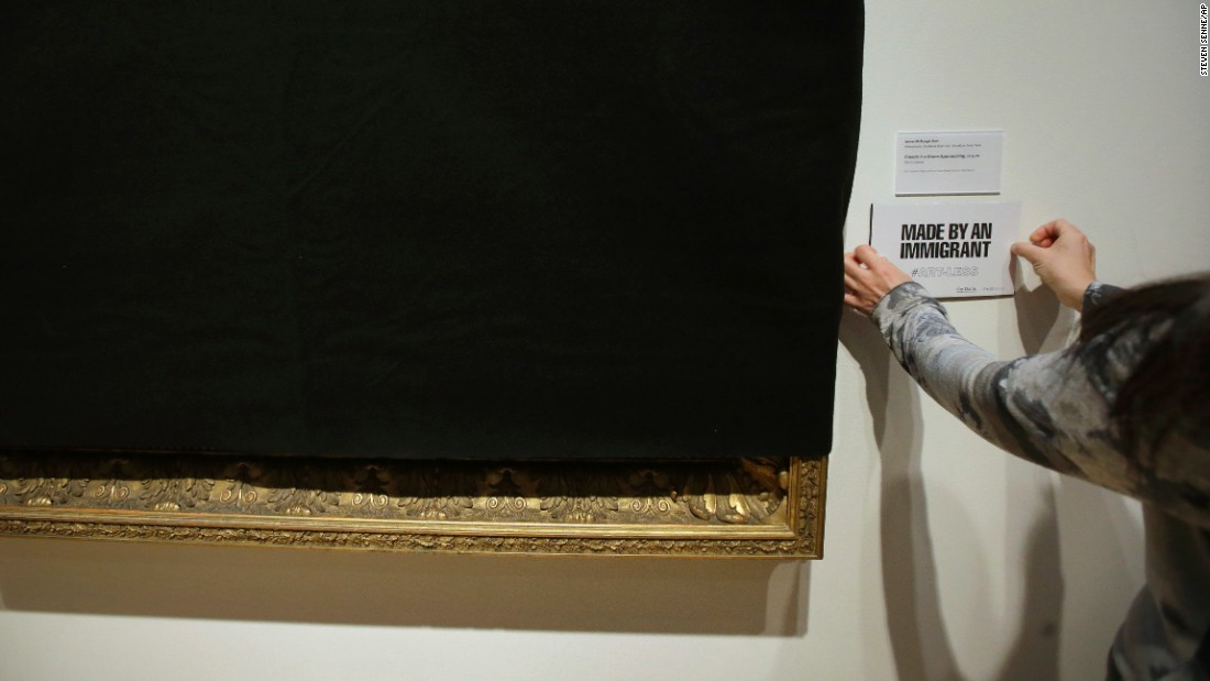 "Tsugumi Joiner, an associate director at the Davis Museum in Wellesley, Massachusetts, places a placard near a shroud-covered painting of Scottish-born artist James McDougal Hart on Thursday, February 16. The museum is <a href=""http://www.cnn.com/2017/02/16/us/museum-removes-art-from-immigrants-trnd/"" target=""_blank"">temporarily covering up artwork</a> that was made by immigrants or given to them by immigrants ""to demonstrate symbolically what the Davis Museum would look like without their contributions to our collections and to Wellesley College."""