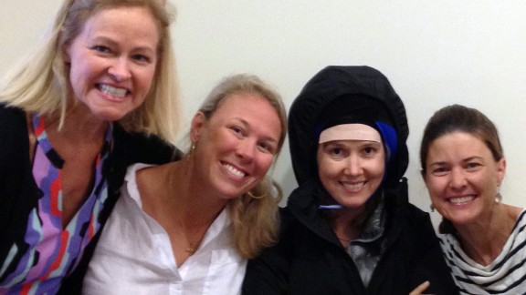 Emily Ferguson wears a cold cap during one of her treatments, surrounded by the friends who help her through it.