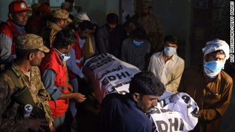 Pakistani volunteers carry the body of a blast victim from a Sehwan hospital Friday.