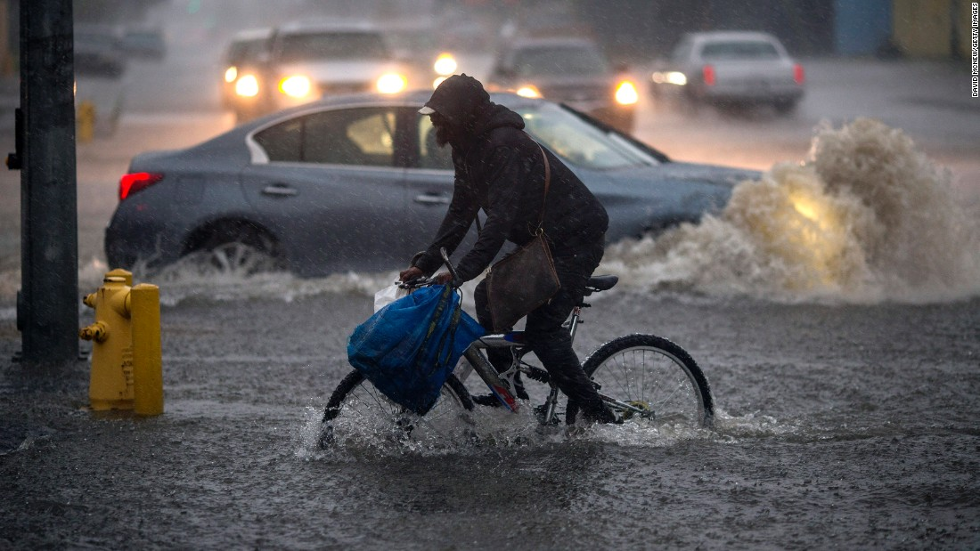 A bicyclist tries to maneuver through a flooded street in the Sun Valley area on February 17.
