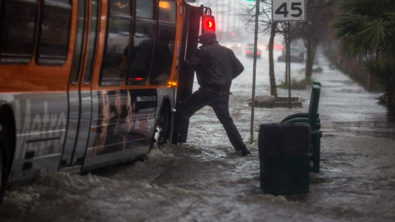 A man attempts to board a bus on a flooded street near the Sun Valley area of Los Angeles on February 17.