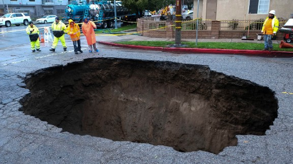 Inspectors check out a sinkhole that formed in Los Angeles' Studio City neighborhood on February 18 after the severe storm hit.