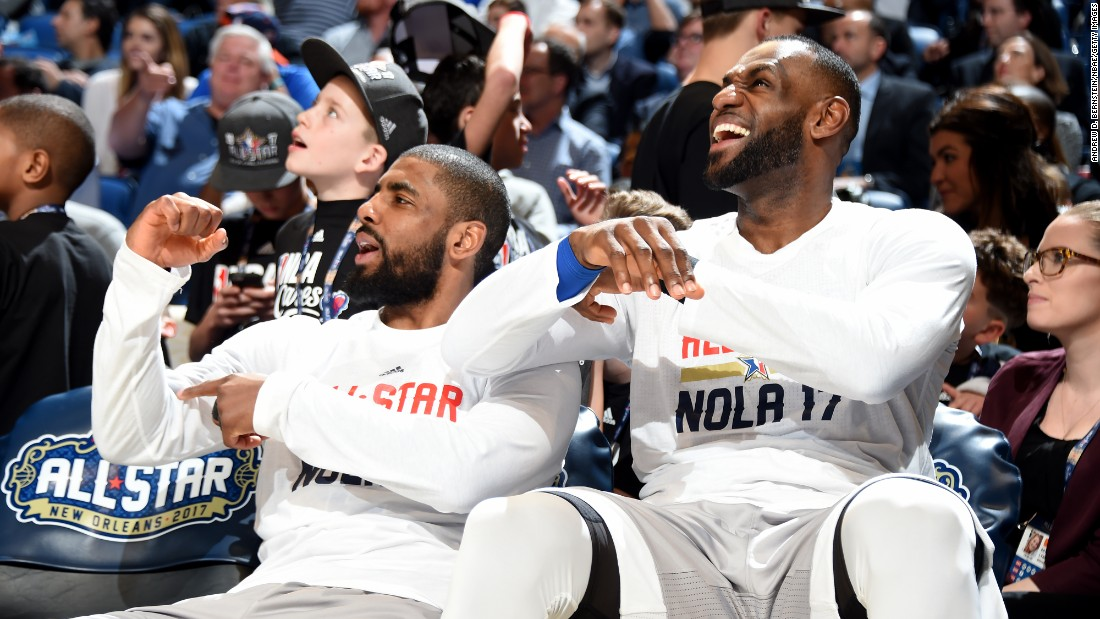 Kyrie Irving, left, and James enjoy a moment while watching from the bench.