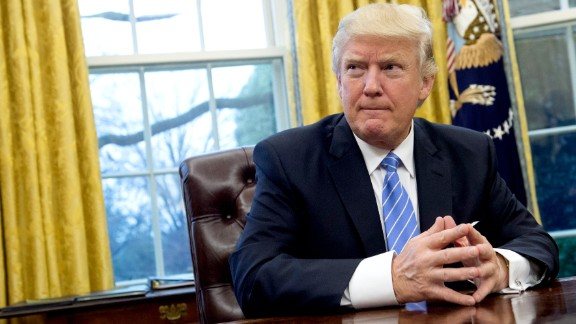 US President Donald Trump prepares to sign several executive orders in the Oval Office of the White House in Washington, DC, January 23, 2017. Trump on Monday signed three orders on withdrawing the US from the Trans-Pacific Partnership trade deal, freezing the hiring of federal workers and hitting foreign NGOs that help with abortion. / AFP / SAUL LOEB        (Photo credit should read SAUL LOEB/AFP/Getty Images)