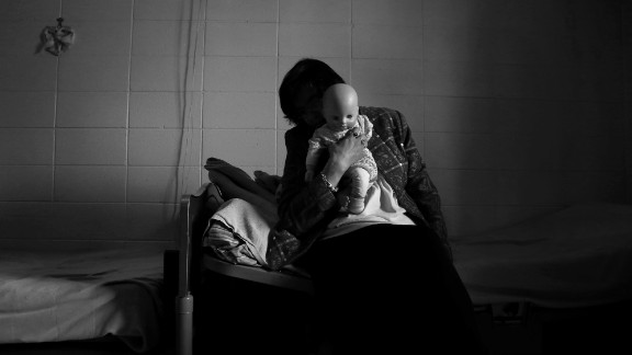 An alleged victim snuggles with a doll she calls Little Missy in her room at a nursing home facility in Haywood County.