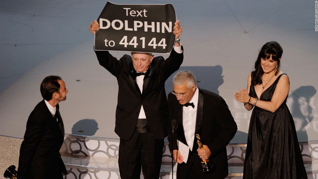 "When Louie Psihoyos and Fisher Stevens won the best documentary feature award for ""The Cove"" at the 82nd Academy Awards on March 7, 2010, they were accompanied on stage by producer Paula DuPré Pesmen and film subject Ric O'Barry. O'Barry walked on stage carrying a sign that prompted the audience to text for more information on how to help curtail the dolphin slaughter depicted in the film."