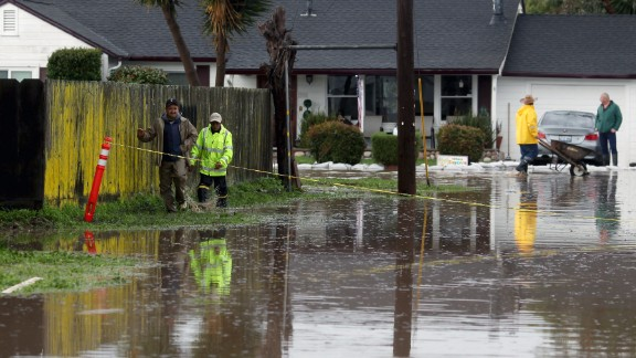 Residents walk down a flooded road in Salinas, California, on Monday, February 20.