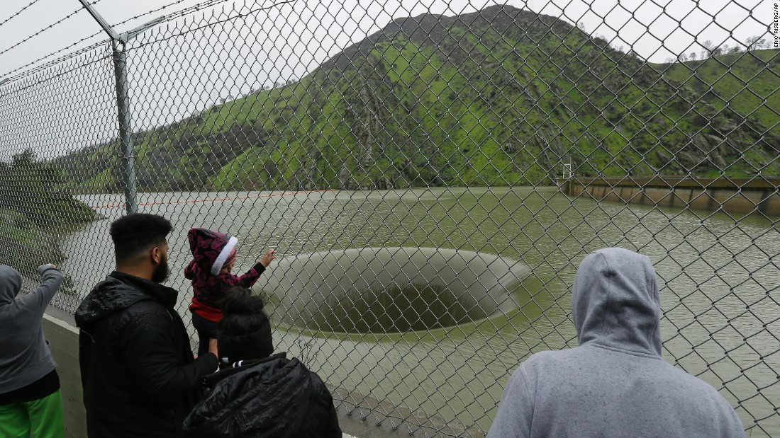 People stop to watch water flow into the iconic Glory Hole spillway at the Monticello Dam on February 20, in Lake Berryessa.  This is the first time in over a decade that water has been high enough to flow into  the 72-foot diameter spillway.