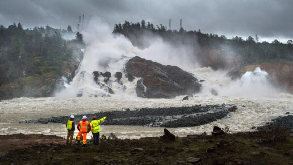 A member of Cal Fire, right, talks to workers on the Oroville Dam project in front of the main spillway in Oroville on February 20. Officials are keeping an eye on the dam after mandatory evacuations last week amid concerns an emergency spillway could fail and threaten communities.
