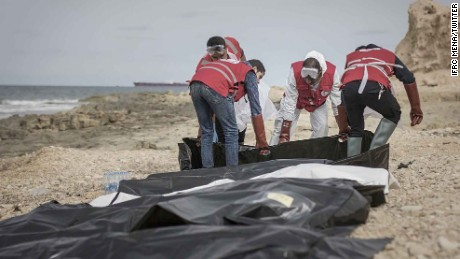 Libyan Red Crescent volunteers collect the bodies of men who drowned and were washed ashore.