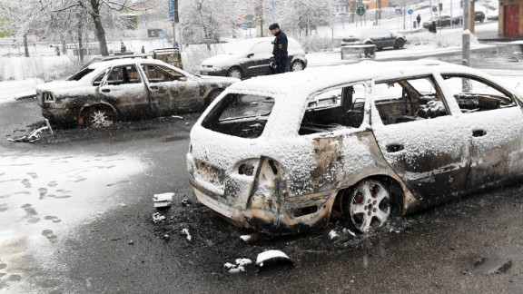 A policeman investigates a burned-out car in Rinkeby, Stockholm, after riots broke out.