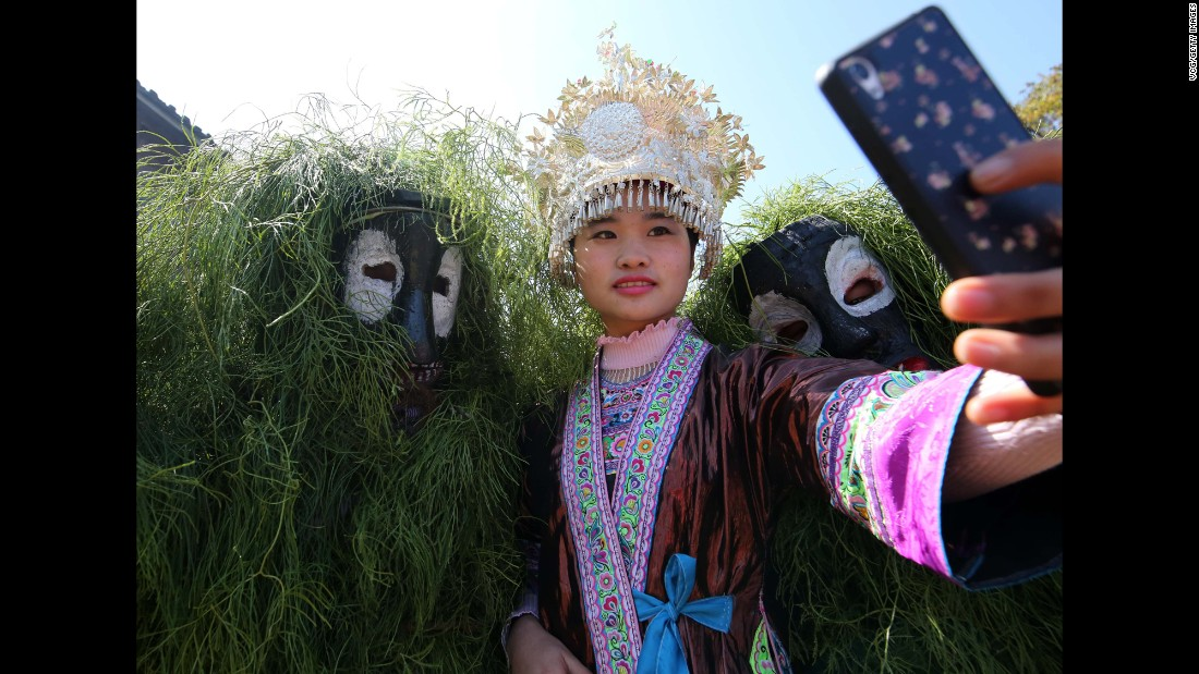 A woman takes selfies with costumed people during the Manggao Festival in Liuzhou, China, on Sunday, February 5.