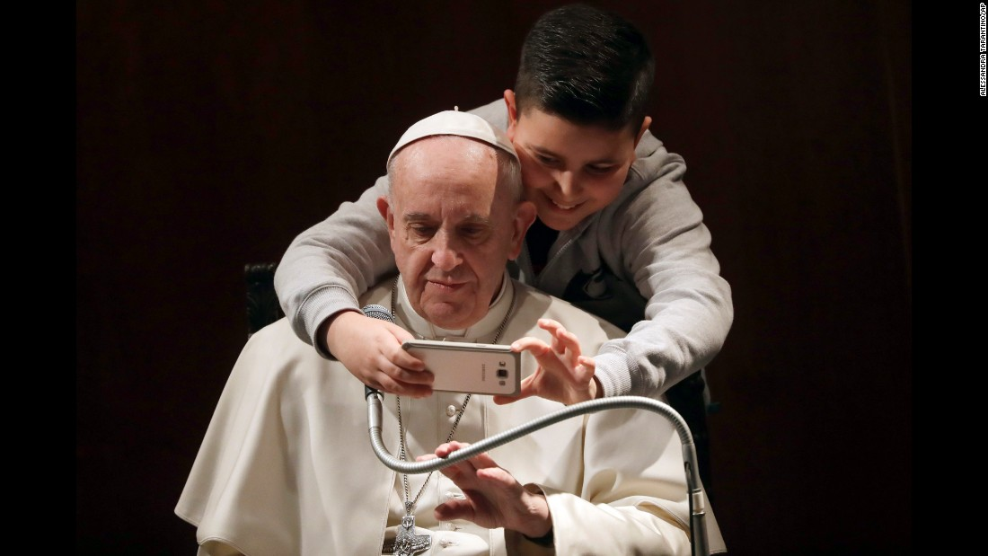 A boy takes a photo with Pope Francis in Rome on Sunday, February 19.