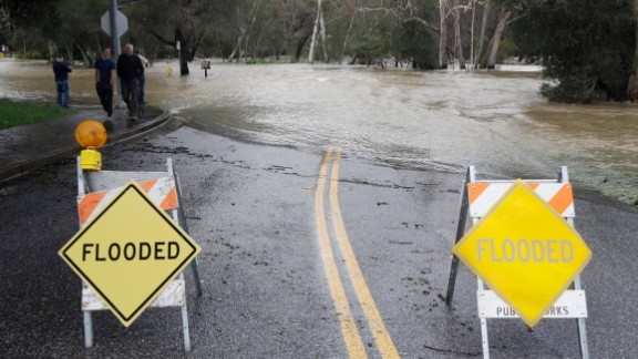 Signs block a road in Morgan Hill, which runs into the overflowing Coyote Creek, on February 21.