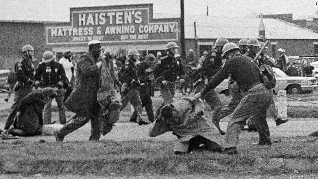 "State troopers swing billy clubs to break up the march on ""Bloody Sunday."" In the foreground, activist John Lewis is being beaten. He suffered a fractured skull. Lewis is now a US congressman."