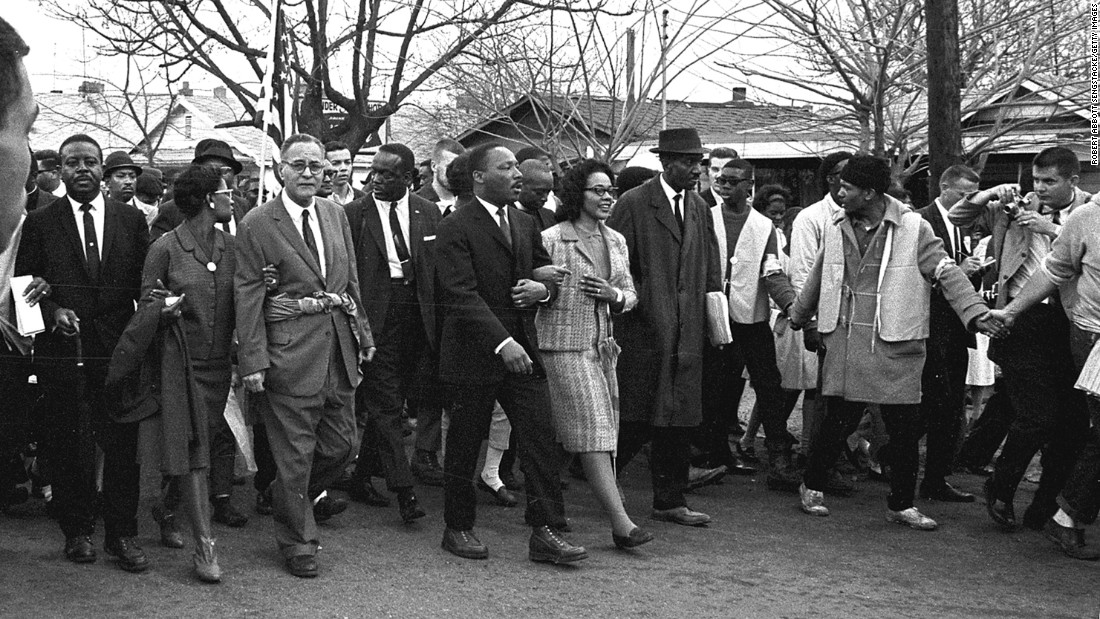 King, center, walks with his wife, Coretta, during the third march on March 21. About 3,200 people marched out of Selma under the protection of federal troops.