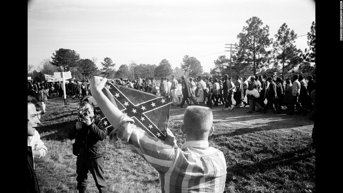 Marchers walk past a young white man holding a Confederate battle flag.