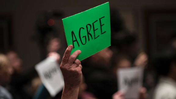 """A constituent holds up sign which reads """"Agree"""" during a town hall meeting with Rep Tom Emmer (R-MN) on February 22, 2017 in Sartell, Minnesota."""