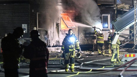 Firefighters tackle a suspected arson attack at a refugee accommodation block in Fagersjo, south of Stockholm, in October 2016.
