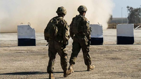 US troops walk as a US Army C-47 Chinook helicopter flies over the village of Oreij, south of Mosul, on February 22, 2017, where a temporary military base has been established for an assault on the city