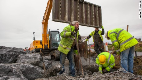 "Workers construct a ""rock-armor"" erosion wall in a residential area of Doonbeg. They say these type of walls are commonplace in Ireland and believe Trump's proposed wall would also stop sea water from entering flood prone areas in Doonbeg. But this residential wall, above, is not being built on protected sand dunes -- which is the primary concern of environmentalists opposed to Trump's wall."