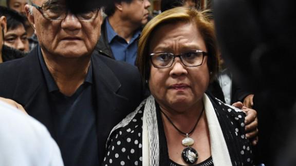 Security personnel escort Sen. Leila de Lima to a press conference Thursday in the Philippines Senate.