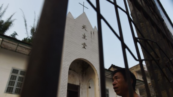 This photo taken on May 11, 2016 shows a villager outside the Catholic church in Changjing, in China's southern Guangxi region.