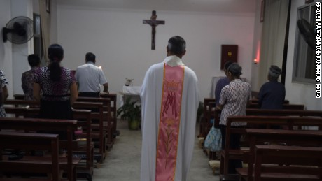 This photo taken on May 11, 2016 shows a priest about to start a mass at the Catholic church in Dingan, in China's southern Guangxi region. The finishing touches are being put to a new museum in Dingan, the village where French missionary Auguste Chapdelaine died in 1856, celebrating the patriotism of his execution and condemning the spiritual opium of religion. / AFP / GREG BAKER / TO GO WITH China-culture-religion-Roman-Catholic-politics,FEATURE by Benjamin Carlson        (Photo credit should read GREG BAKER/AFP/Getty Images)