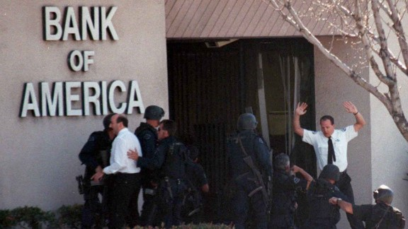A bank employee holds up his hands as police search for more robbery suspects inside the bank.