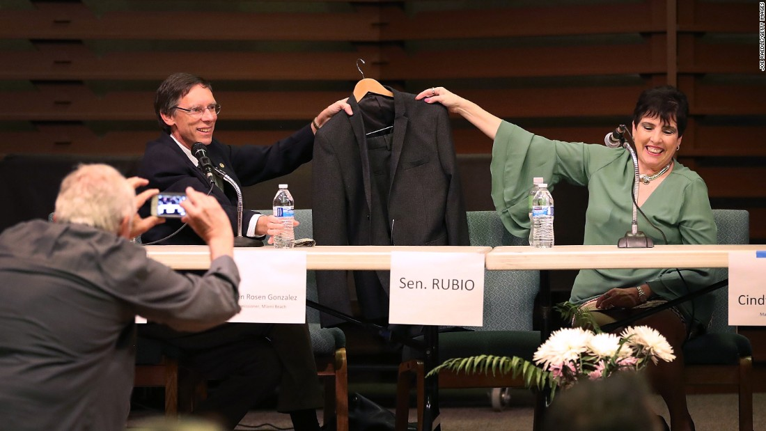 "Elaine Geller and Phil Stoddard, the mayor of South Miami, Florida, hold up a suit jacket to represent US Sen. Marco Rubio during a town hall event in Miami on Thursday, February 23. Rubio <a href=""http://www.cnn.com/2017/02/22/politics/liberals-marco-rubio-empty-chair-town-hall/"" target=""_blank"">was traveling in Europe</a> on Senate business."
