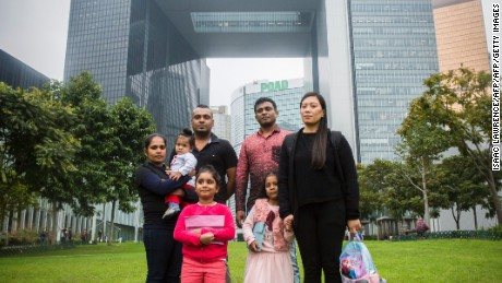 Sri Lankan refugee Supun Thilina Kellapatha (3rd L), 32, his partner Nadeeka (L), 33, with their baby boy Dinath, daughter Sethumdi, 5, Sri Lankan refugee Ajith Puspa (3rd R), 45, and Filipino refugee Vanessa Rodel (R), 40, with her daughter Keana, 5, pose for a photo in front of the government buildings of Hong Kong on February 23, 2017.