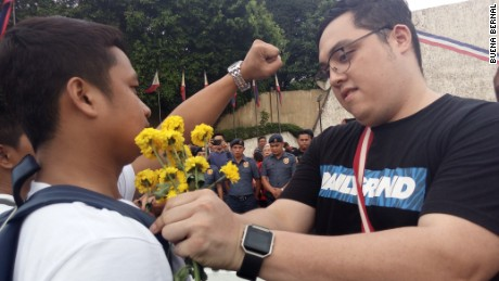 An anti-Duterte protester apologizes with a flower to a Duterte supporter.