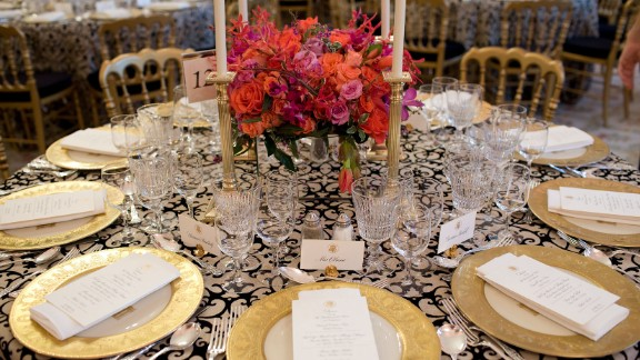 White House State Dining Room 2010. Black and white-patterned linens and bright coral flowers create an elegant backdrop with table décor selected from the historic White House collection: gold-rimmed Clinton base plates, coral-red Reagan china, Charleston candlesticks, King Charles flatware, and eagle motif place card holders. Illuminated with votive and taper candles and mirrored centerpiece containers capturing the candlelight and flowers.