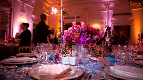 """White House State Dining Room 2011. A vivid bouquet of orange and fuchsia flowers with accents of hot pink Phalaenopsis orchids makes a strong statement for the annual National Governors Association Dinner at the White House state dining room. The historic """"Charleston"""" candlesticks are wrapped with blooming jasmine vine. The Lady Bird and President Johnson china service, featuring wildflowers from across America, reflects the gathering of Governors from all 50 states."""