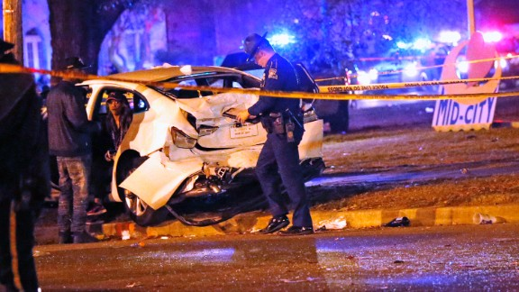 Police officers chat with a man in a car that was struck by a pickup.