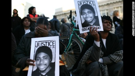 Protesters carry signs with a picture of Oscar Grant during a demonstration at Oakland City Hall on January 14, 2009.