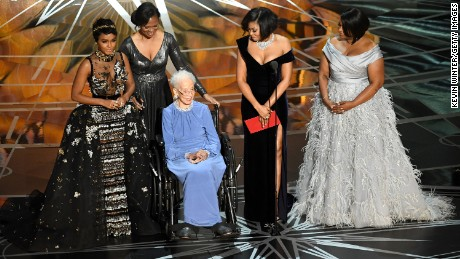 "Katherine Johnson (in blue dress) was honored by ""Hidden Figures"" actors Janelle Monae, Taraji P. Henson and Octavia Spencer during the Academy Awards in 2017. Henson played Johnson in the movie."