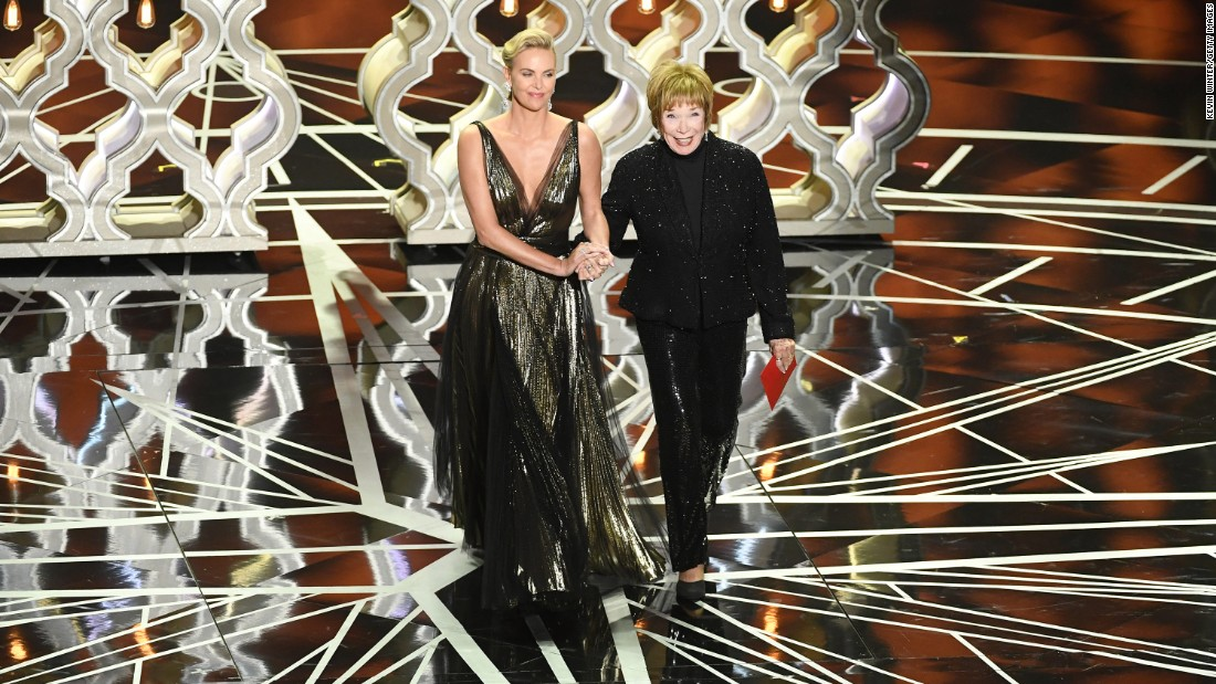 Charlize Theron, left, and Shirley MacLaine walk on stage to present an award. Theron said MacLaine inspired her to get into acting.