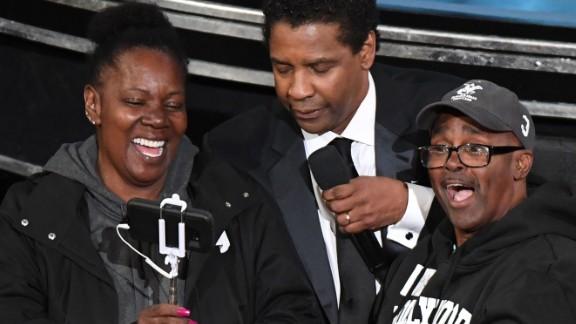 "Gary Coe, aka ""Gary from Chicago,"" and his fiancee, Vickie Vines, meet Denzel Washington at the 89th Oscars on Sunday."