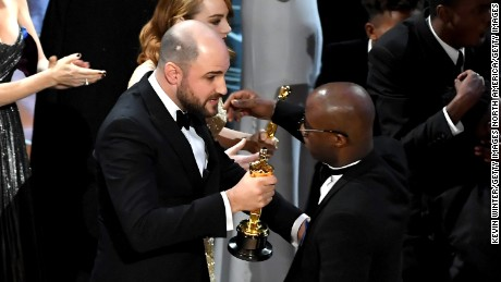 "''La La Land"" producer Jordan Horowitz hands over the Best Picture award to ""Moonlight"" writer/director Barry Jenkins following a presentation error onstage during the 89th Annual Academy Awards. (Photo by Kevin Winter/Getty Images)"
