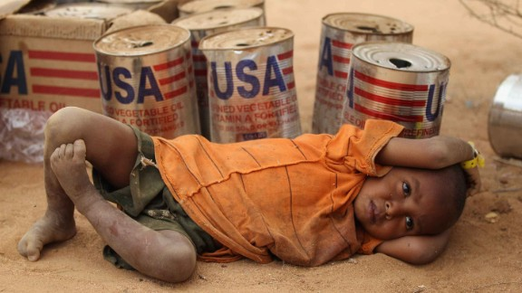 DADAAB, KENYA - JULY 19:  A young boy rests by empty USAID vegetable oil tins in the Dagahaley refugee camp which makes up part of the giant Dadaab refugee settlement on July 19, 2011 in Dadaab, Kenya. The refugee camp at Dadaab, located close to the Kenyan border with Somalia, was originally designed in the early 1990s to accommodate 90,000 people but the UN estimates over 4 times as many reside there. The ongoing civil war in Somalia and the worst drought to affect the Horn of Africa in six decades has resulted in an estimated 12 million people whose lives are threatened.  (Photo by Oli Scarff/Getty Images)